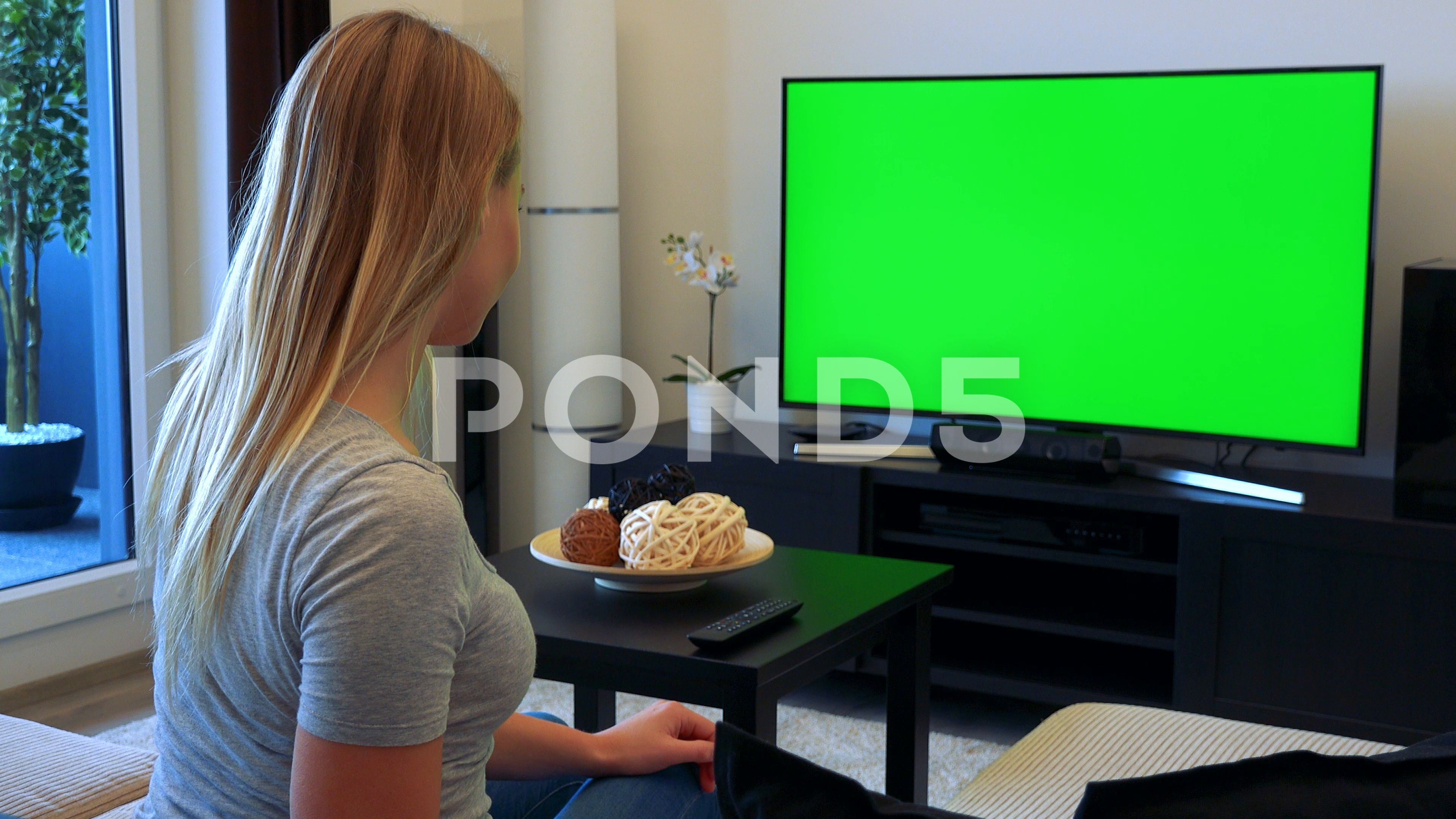 Woman Sits On Couch In Living Room Watches Tv Green Screen And Agrees To Camera Stock Footage Living Room Watches Greenscreen Couches Living Room Living Room