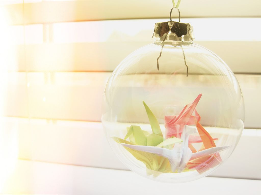 origami cranes inside clear christmas ornaments clear