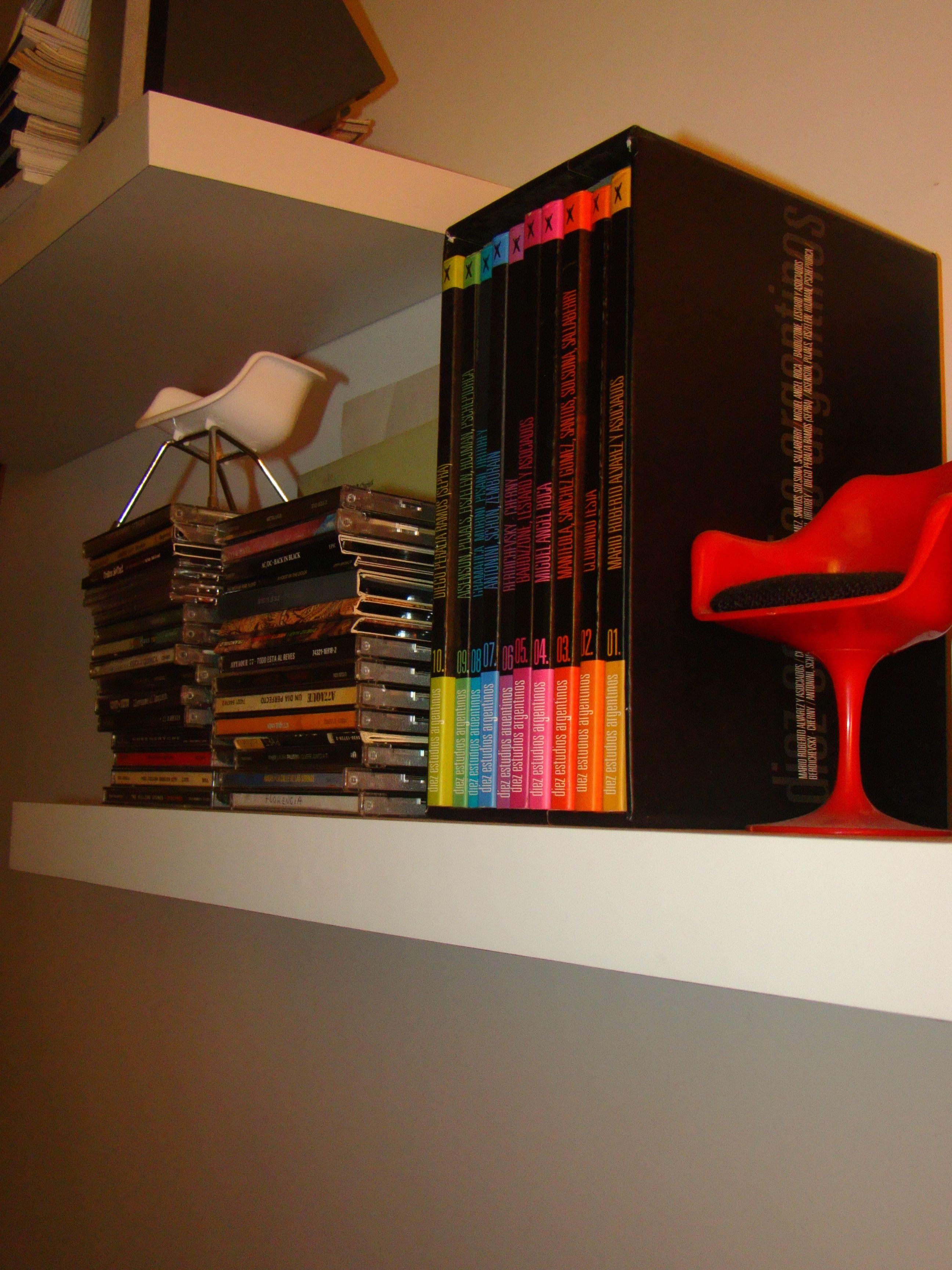 estantes con ménsula escondida, libros de arquitectura , cd y mini-sillas de diseño
