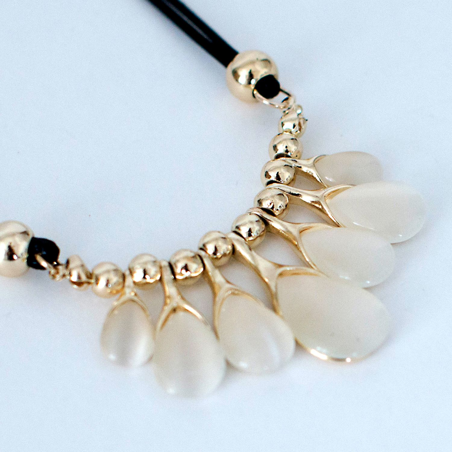 collections-by-h | NECKLACES     £12.00            Gold and opal effect semi -precious stone pendent necklace, 7 stones draped of glistening gold's and set off against and background of bold black.