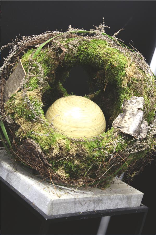 De urn wordt omringd door een versiering in natuurlijke stijl. Mos, takken, schors en een gras vormen een omhulsel voor iemand die erg van de natuur hield.