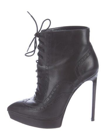 4e784199bef Black leather Yves Saint Laurent pointed-toe platform booties with brogue  trim, stacked stiletto heels and lace-up closures at uppers.