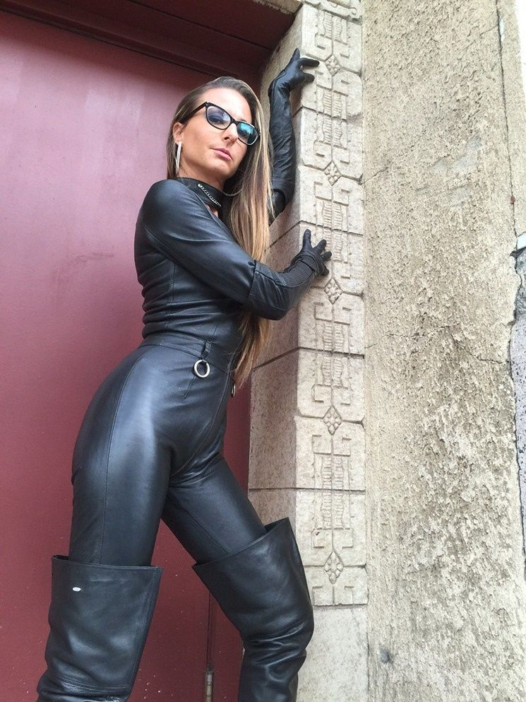 Bespectacled blonde babe in black leather catsuit ant thigh boots