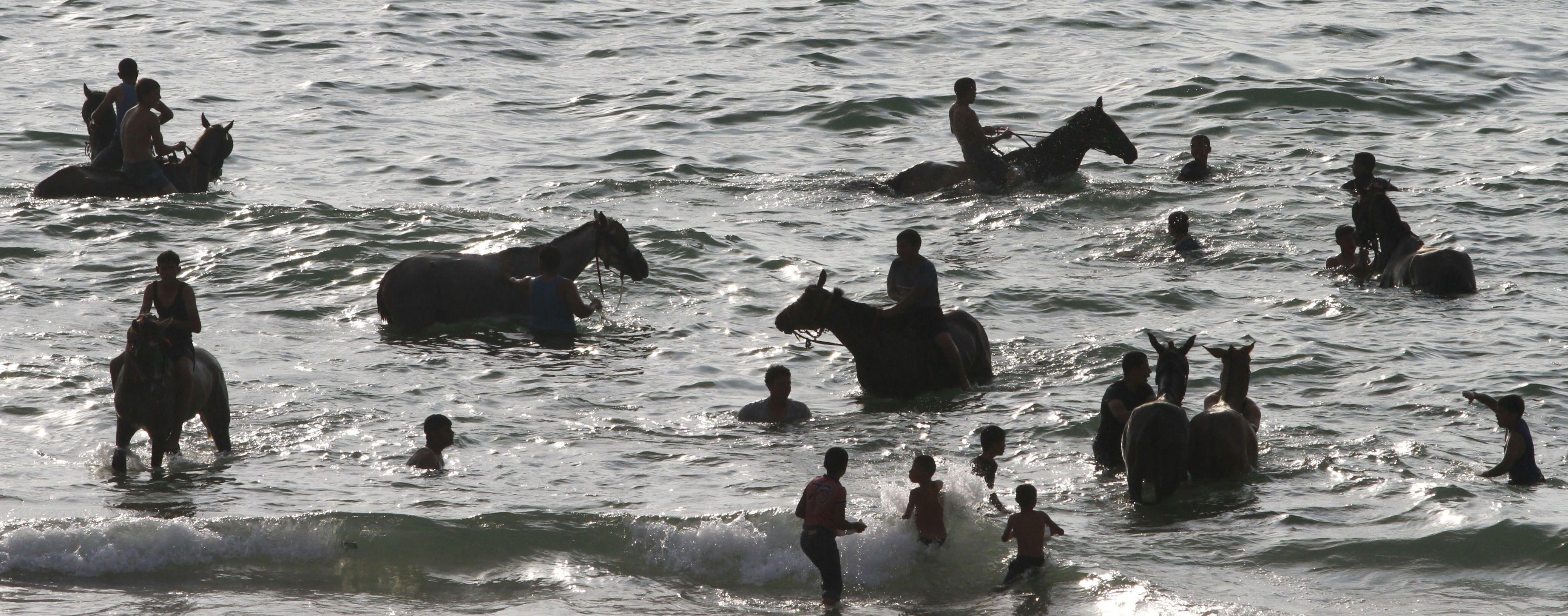 Palestinos montan sus caballos en las aguas del mar Mediterráneo en la Franja de Gaza (Hatem Moussa/AP)