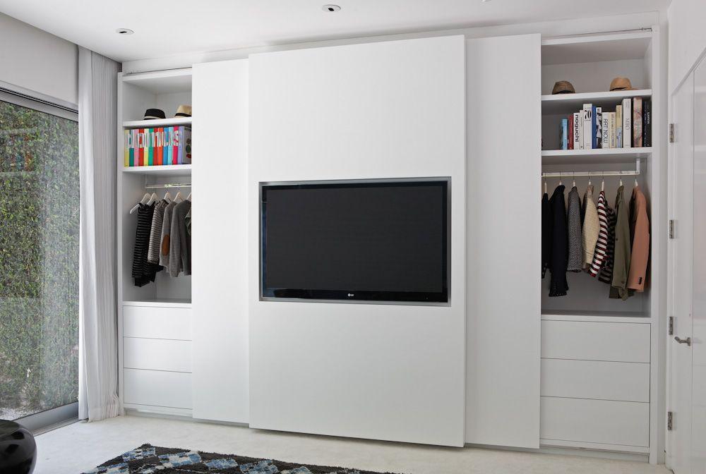 In de schuifdeur van deze strakke slaapkamer inbouwkast is de tv