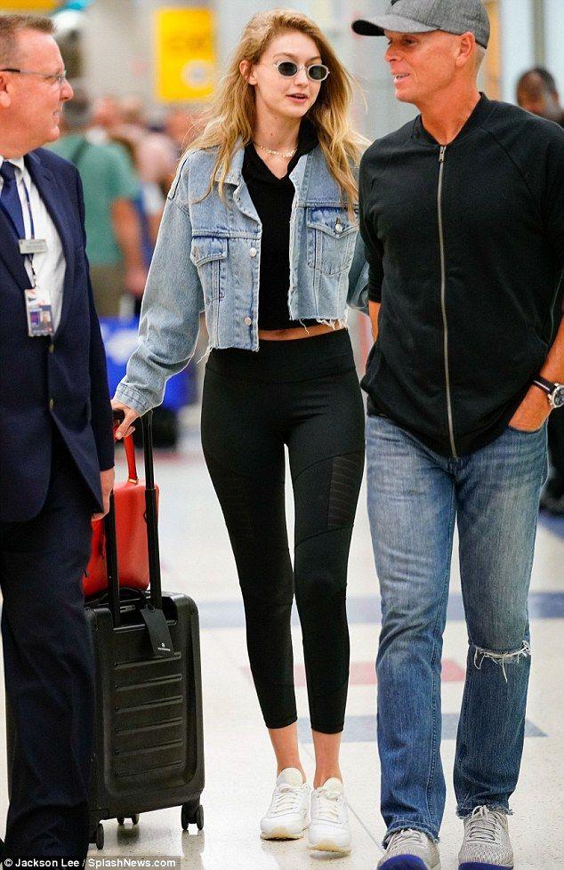 Gigi Hadid teases taut tummy in denim jacket and black crop top at JFK #gigihadid