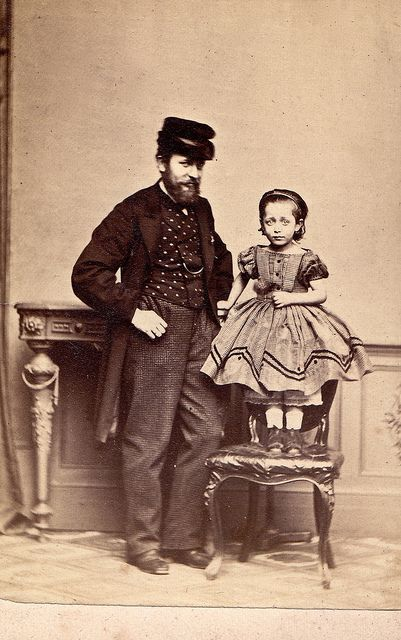 Unknown man and girl, circa 1867. Stand behind the chair supports the deceased child. It looks like she is also holding the tell-tale broken rose, also.