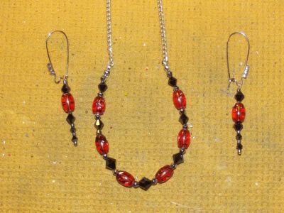 This is another of my unique beautiful hand crafted sets. I took and beaded orange glass splatter beads and black bi cone swarvoskis,and clear silver glass spacers and hung them from a silver tone neck chain. The matching earrings are made of the same beads,but there are 3 clear cut crystals in silver tone settings on the silver toned ear wires. $25