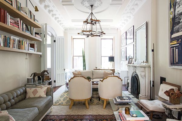 A Long Living Room Is Divided Into THREE Spaces With Layered Rugs And Lots Of Vintage