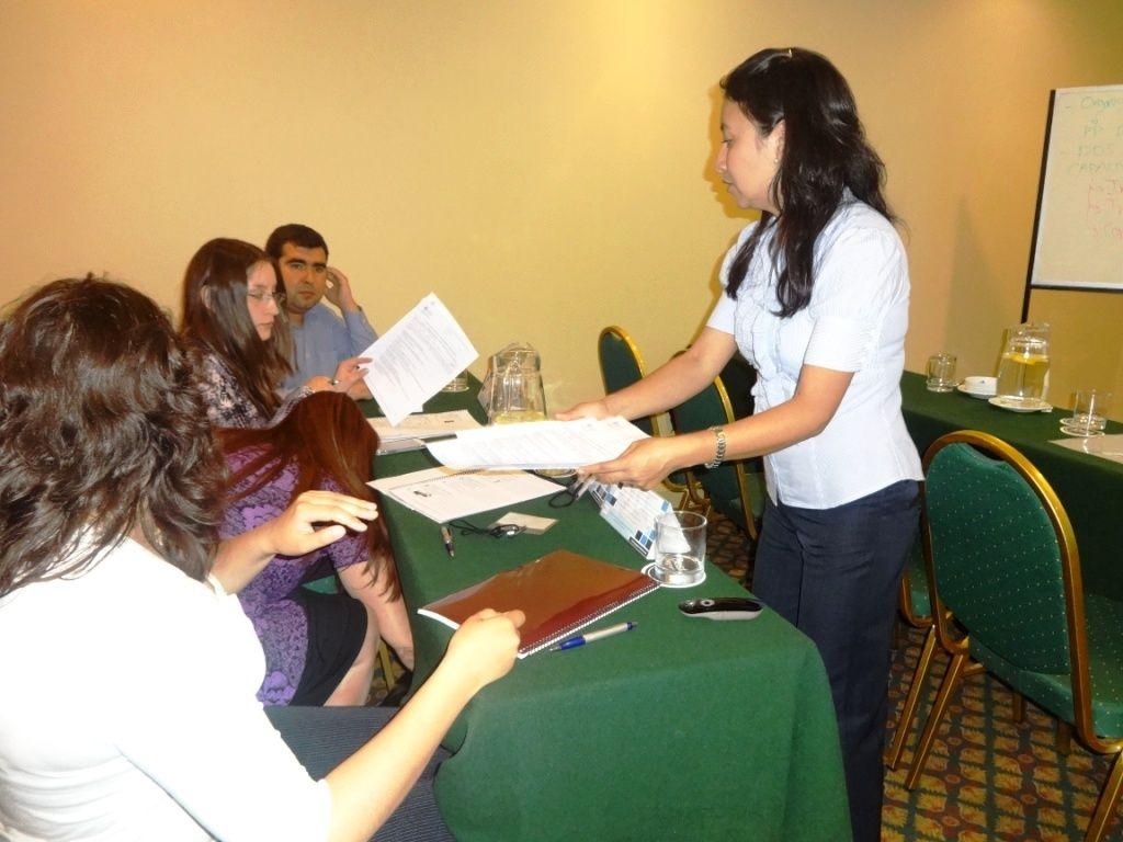 La ponente recibiendo los examenes de los asistentes para su evaluación.