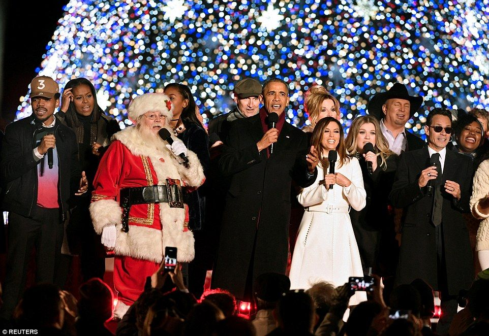 Obama (C) joins Santa Claus for a concluding Christmas carol during the 94th Annual National Christmas Tree Lighting with (L-R) Chance the Rapper, First Lady Michelle Obama, James Taylor, Eva Longoria, Kelly Clarkson, Garth Brooks and Marc Anthony