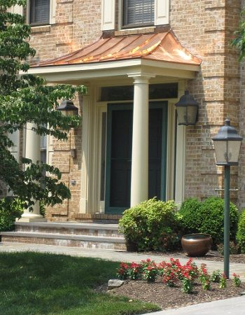 Copper Portico With Tapered Columns And Stone Patio