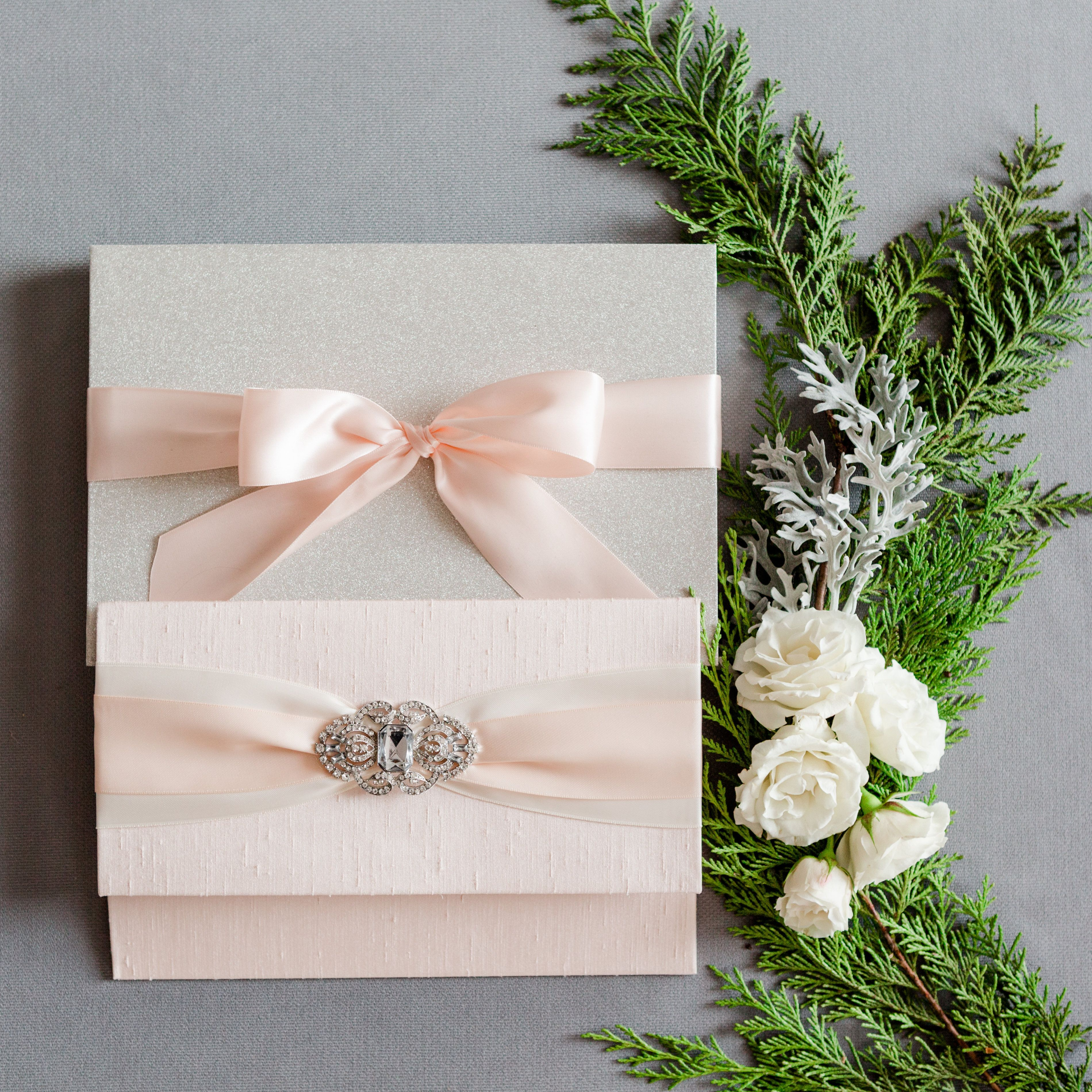 Blush colored silk wrapped folio with two layers of ribbon and a