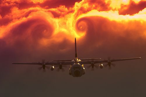 Vortices of the best kind follow this Coast Guard C-130J as it breaks from the clouds.