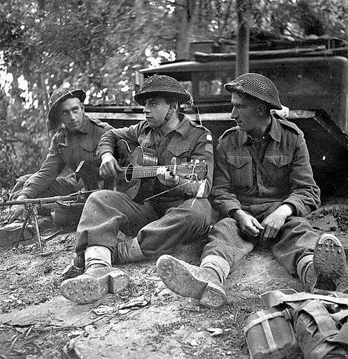 In this photo Pte. W.J. Lutz, Pte. J.D. Hines (with guitar), and Pte. R. Lecoeyer relax beside dugout during the Battle of Caen. 10 July 1944, Caen, France.