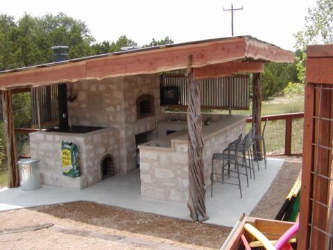 Covered outdoor kitchen with pizza oven and bar.