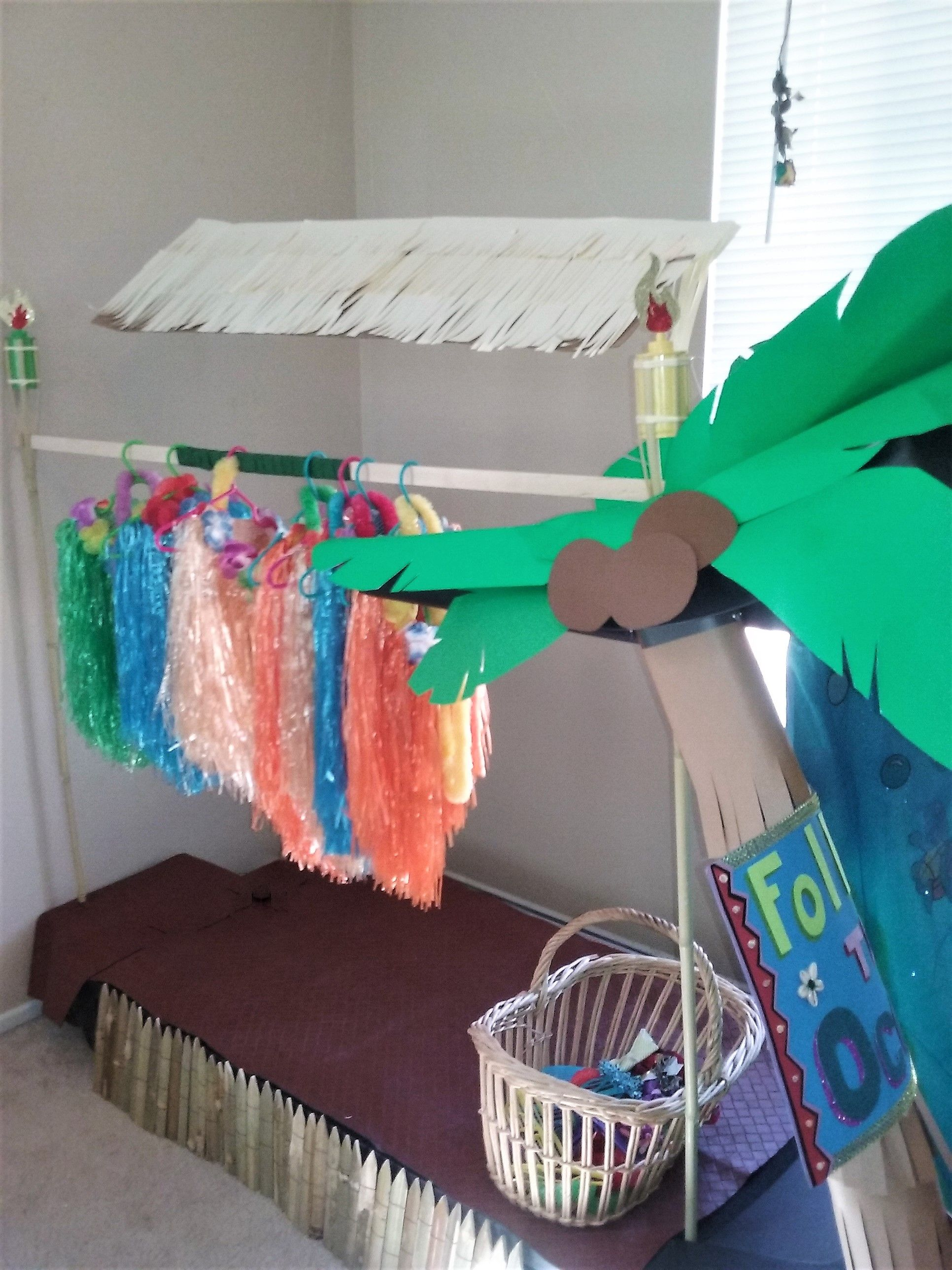 Favors dress up station. skirt and leis Custom decorations created around a  treadmill that was too heavy to move! Tiki torches, cabana and palm trees!
