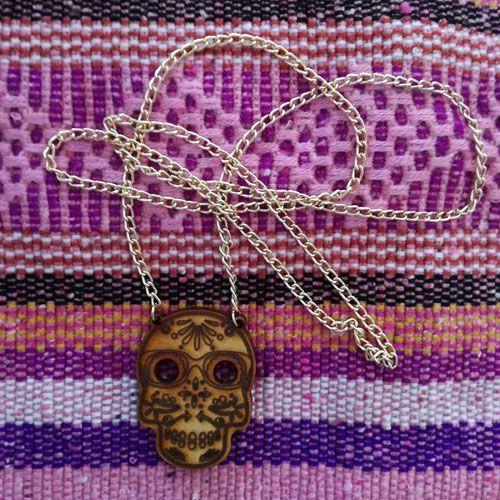 El collar Sugar Skull, es una pieza artesanal hecha de madera con un cristal mineral y cadena bañada en oro.