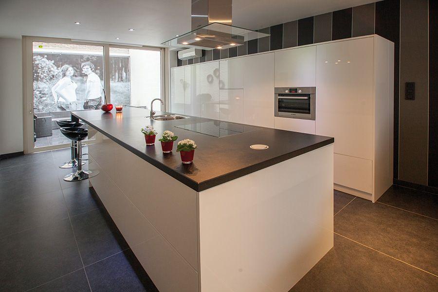 Hoogglans keuken met kastenwand en kookeiland hoogglans gecombineerd met natuursteen werkblad - Keuken met tafel ...