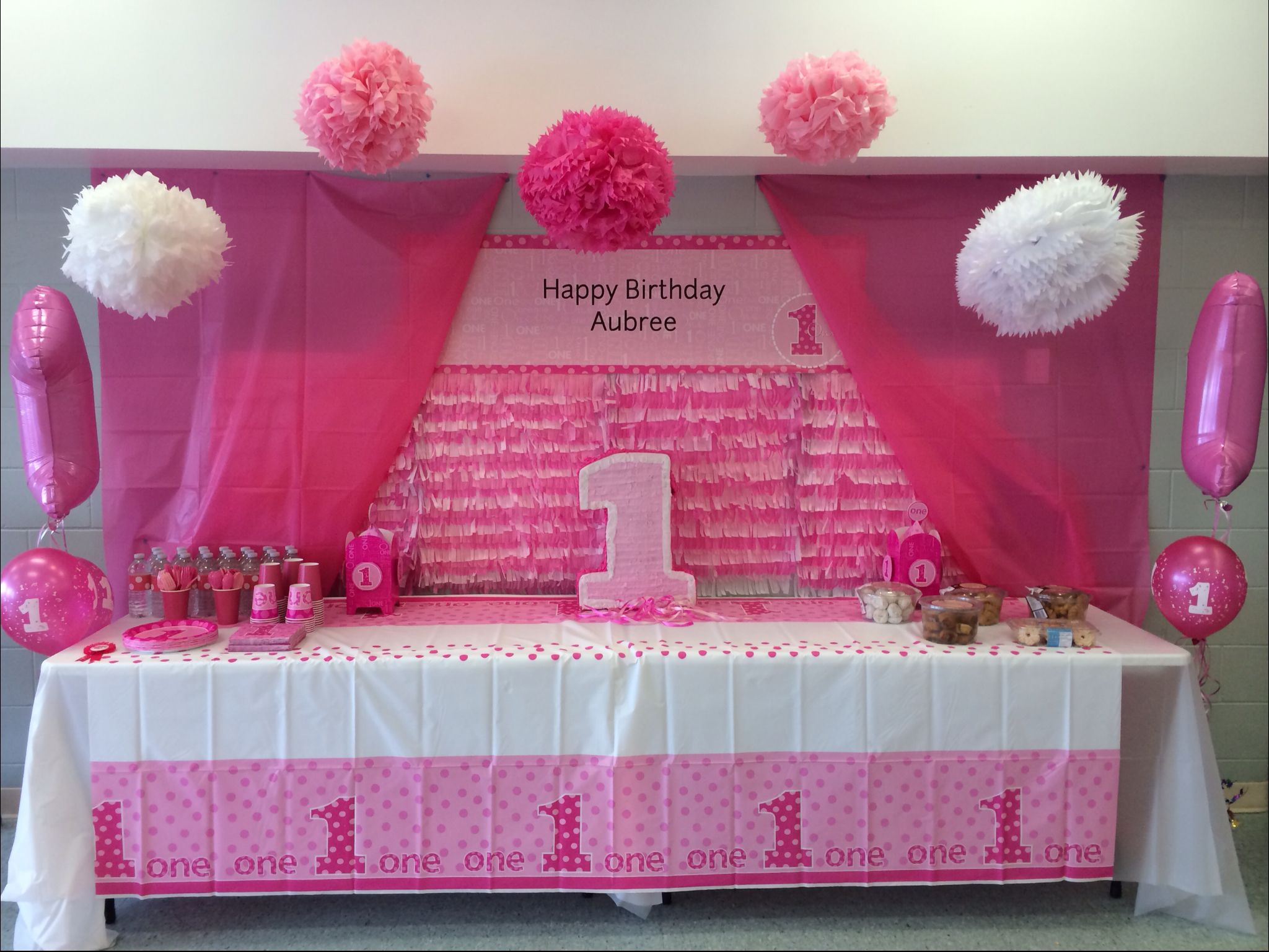 First birthday decorations for a pink them DIY pompoms and backdrop
