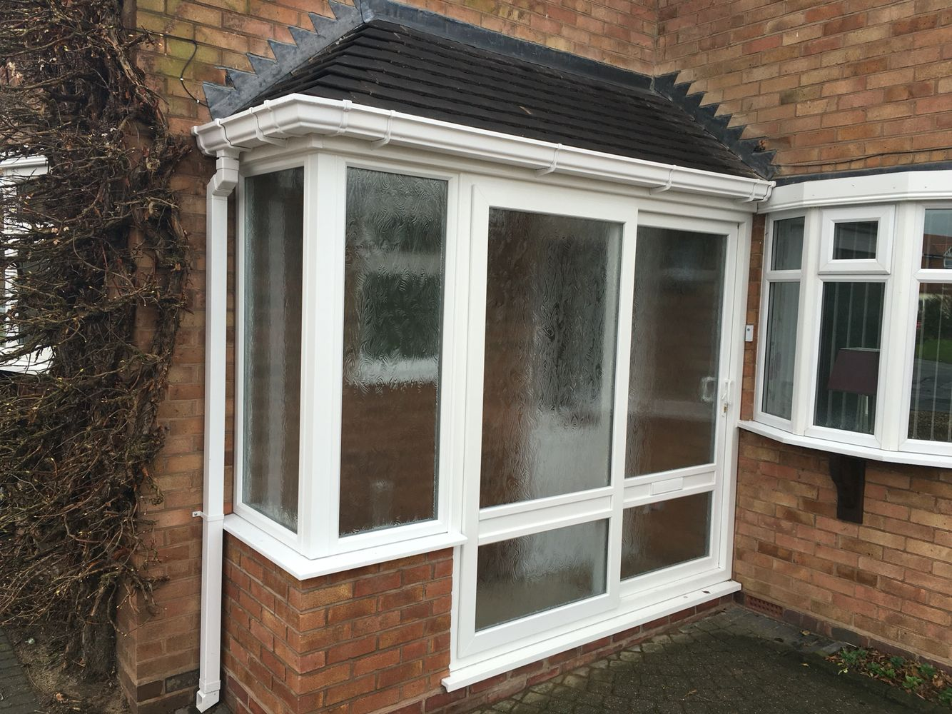 Hipped lean to porch with small tiles upvc sliding patio for Pvc porch door