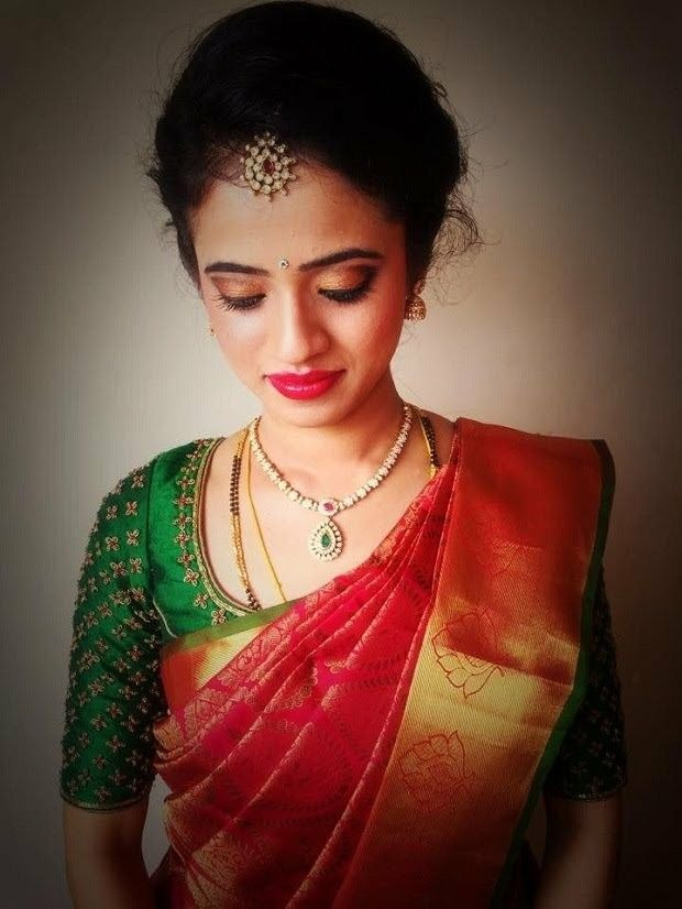 540b145850f296 Red silk saree with green blouse perfect combination for an Indian bride.  Light necklace and mangtikka enhancing the beauty.