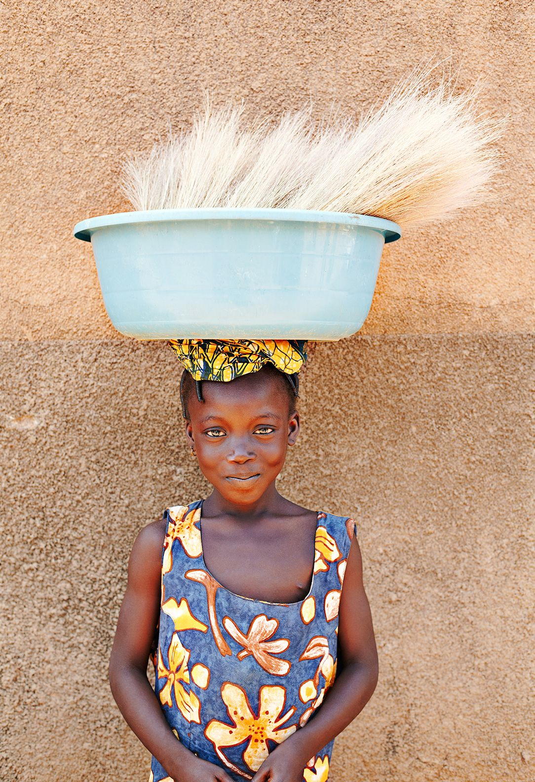 Young girl standing with a large bucket balanced on her head