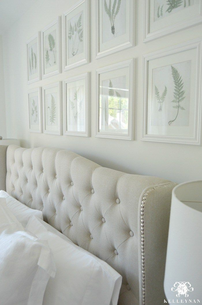 Botanical fern gallery wall in white bedroom above tufted - Above the headboard decorating ...