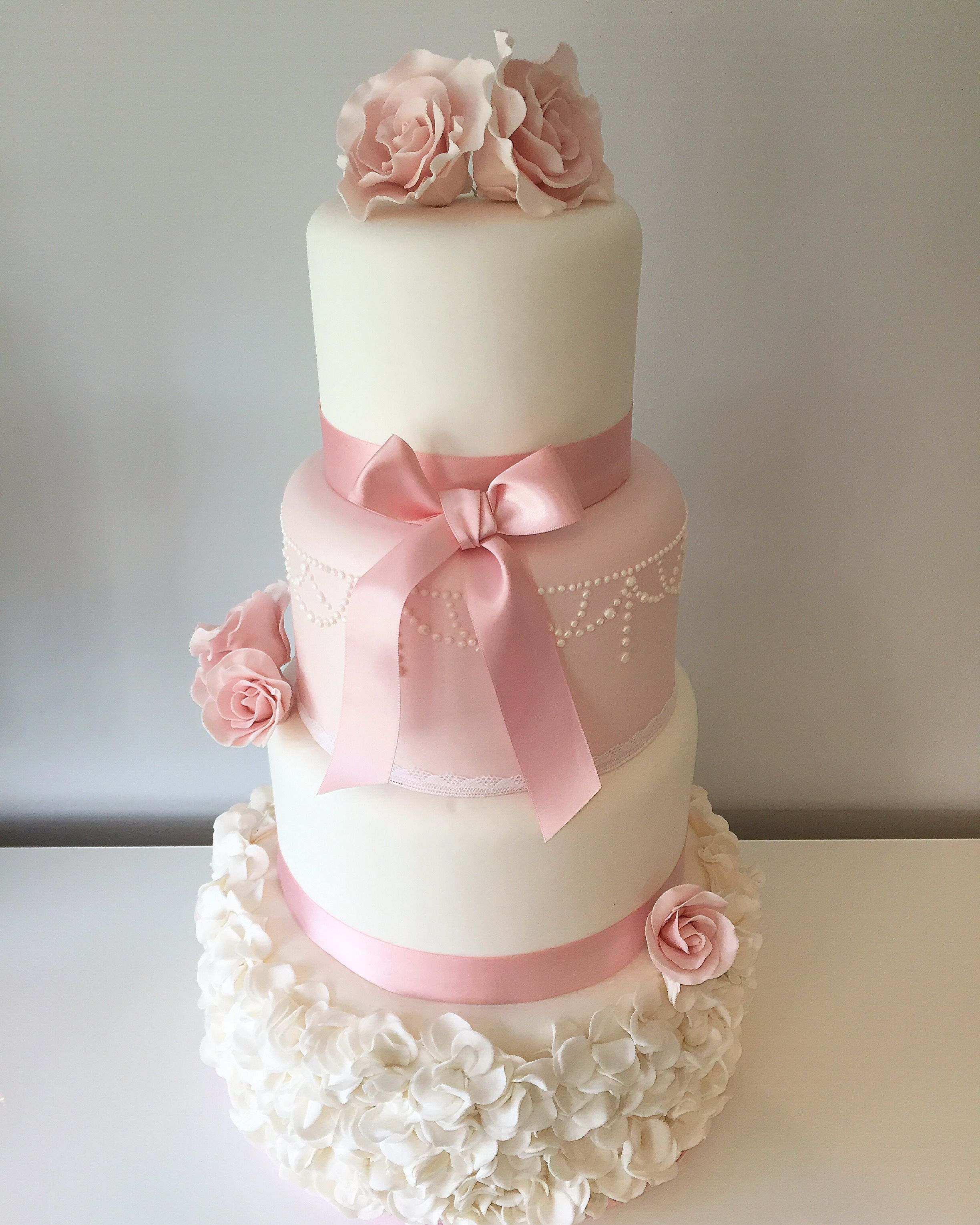 Traditional elegance with rounded edges, buttercream crumb coat used on this cake. This cake would fit well in any traditional English wedding with its ruffles, delicate piped work and roses.