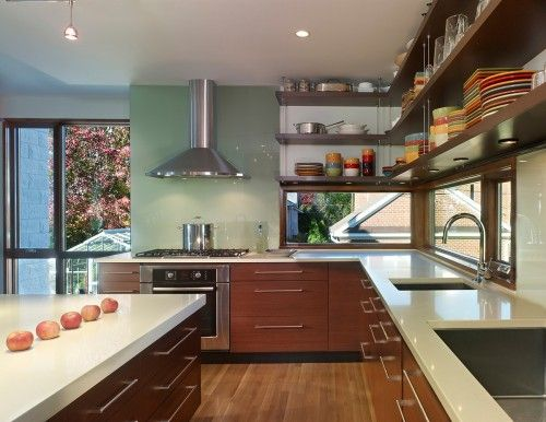 Windows below cabinets add interest and open up a kitchen.  I've used this strategy to great effect in my designs.