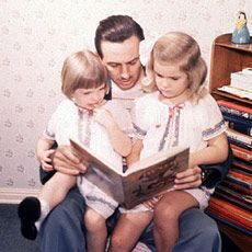 Walt Disney reading with daughters Diane and Sharon.
