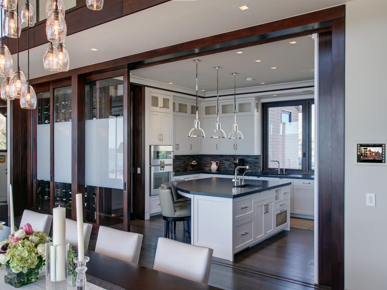 A sleek open kitchen is connected to the dining room via sliding glass doors the look feels for Sliding door design for kitchen