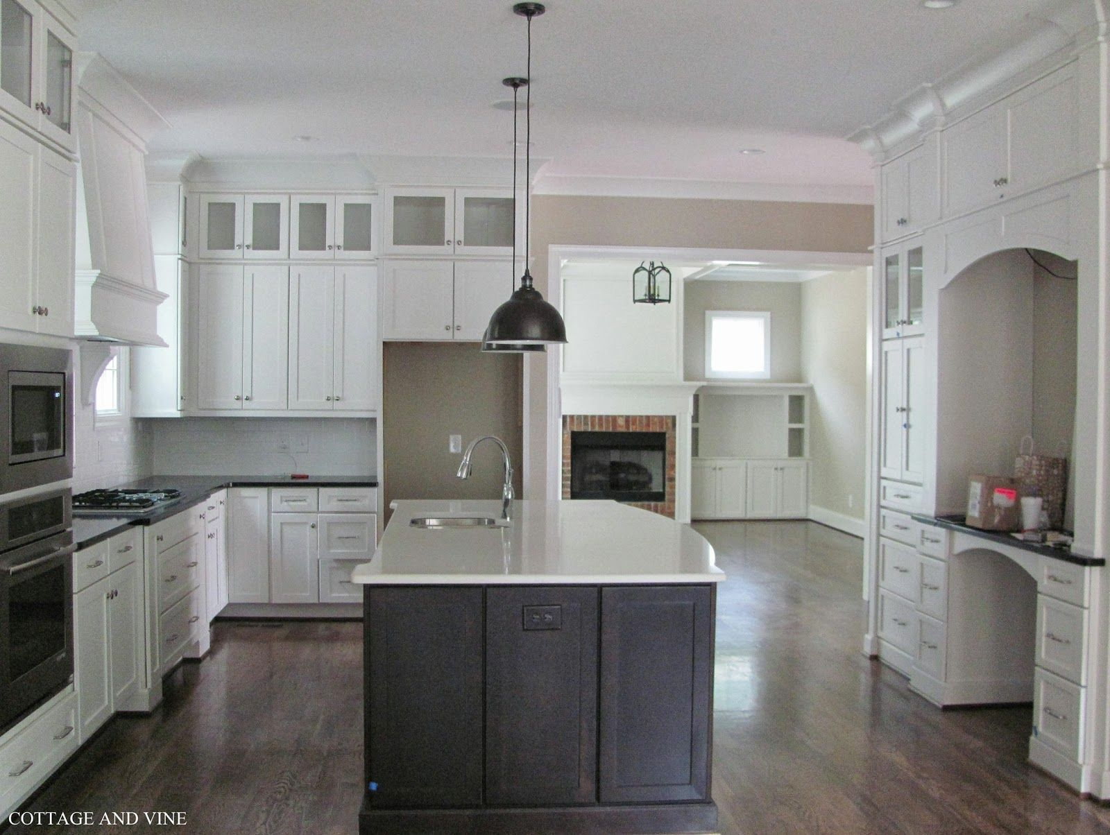 Stylish white kitchen cabinets and hanging dining lights over