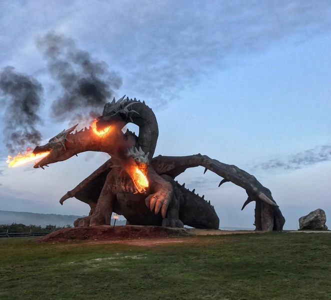 A statue of a threeheaded fire breathing dragon in