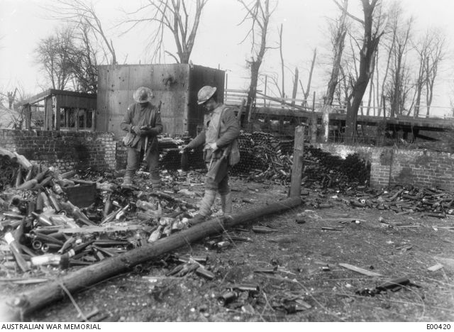 Two members of the 22nd Battalion check out the stacks of empty wine bottles left by the Germans at Bapaume.