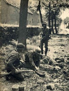 Soldiers with metal detector. Possibly disarming mines. SOldier in front…