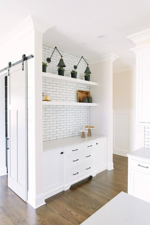 Gold and black swing arm sconces are mounted in a kitchen nook above white floating  shelves - Gold And Black Swing Arm Sconces Are Mounted In A Kitchen Nook