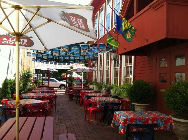Colorful flags, flowers and umbrellas adorn the recently-opened Firehouse Beer Garden, serving German sausages and craft beers. Photo: Micha...