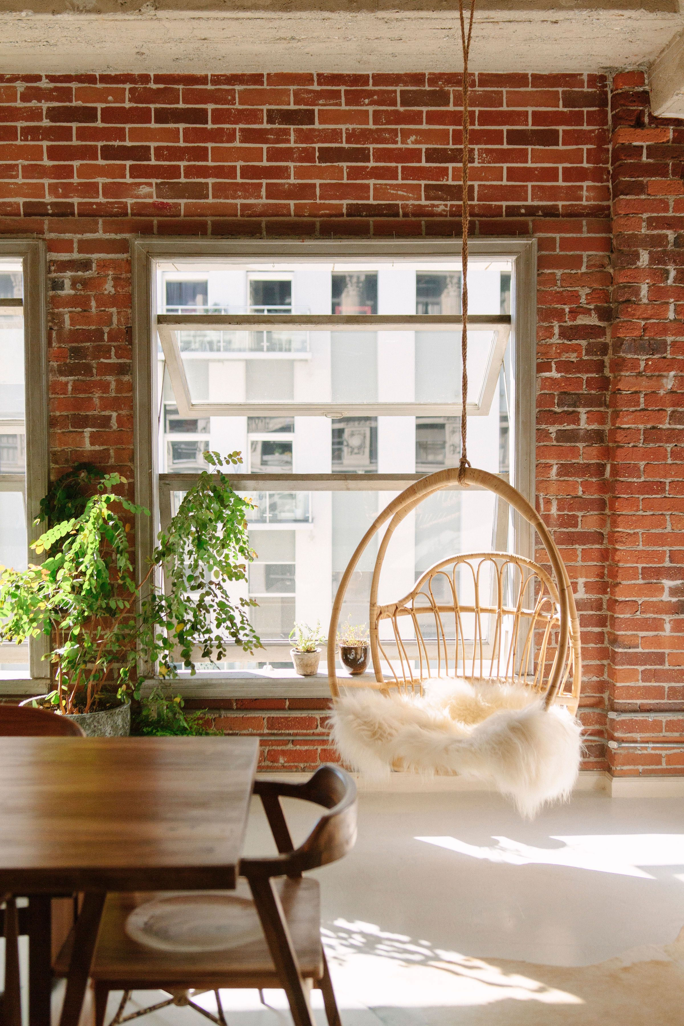 Large Windows With Views Of Downtown La Exposed Brick And A Hanging Chair Click To See The Rest Of This Indust Loft Decor Exposed Brick Boho Loft Apartment