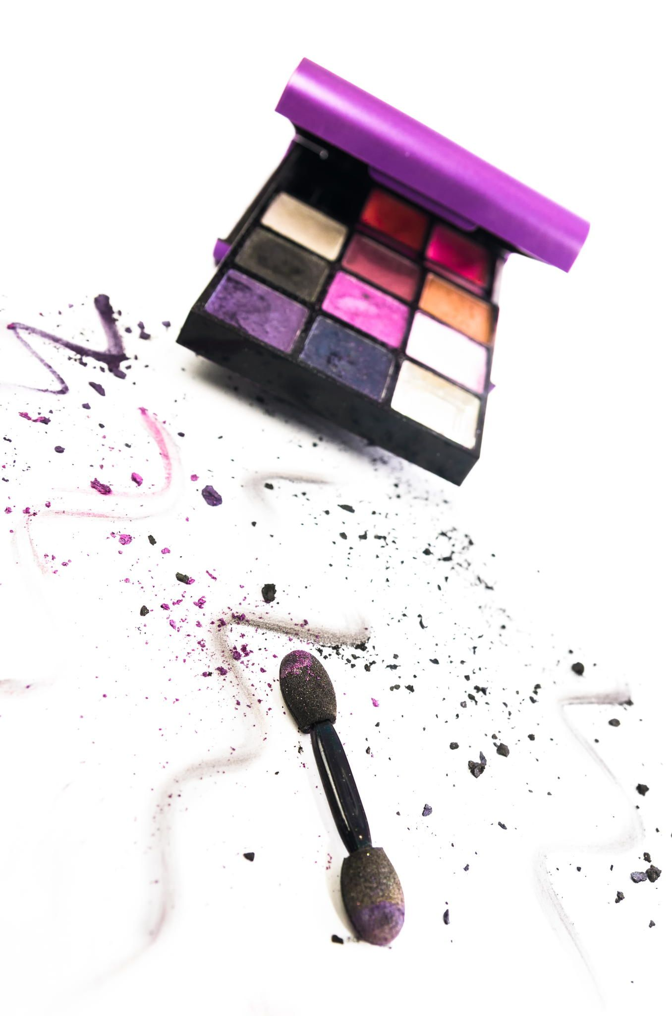 Colourful eye makeup - Artistic arrangement of colourful eye makeup in a box with an applicator and scattered remnants and squiggles of powdered cosmetic in the foreground on white