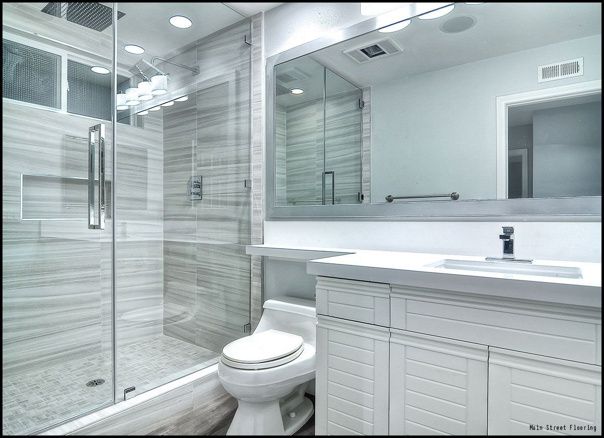 A sleek and modern bathroom with a white vanity and gray ...