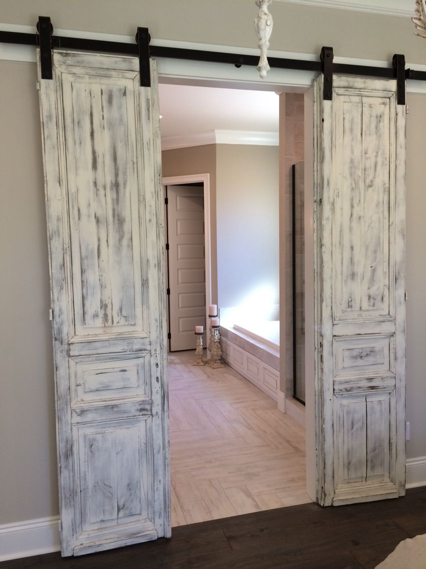 master bath entrance with our antique french paneled doors whitewashed and hung barn door style