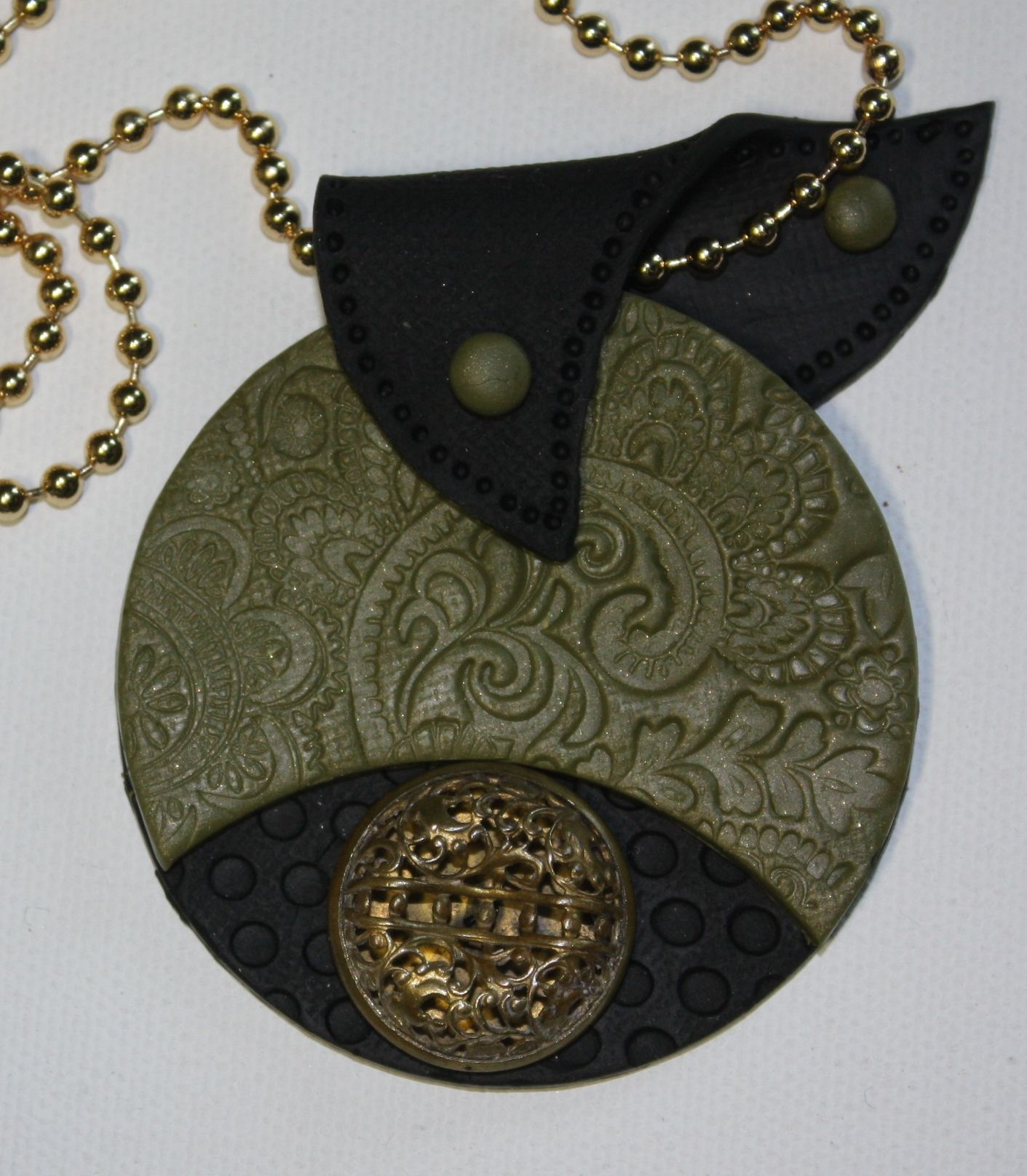 Whimsical bail, a tapestry pattern and vintage floral button combine to give this polymer clay pendant a classy look.