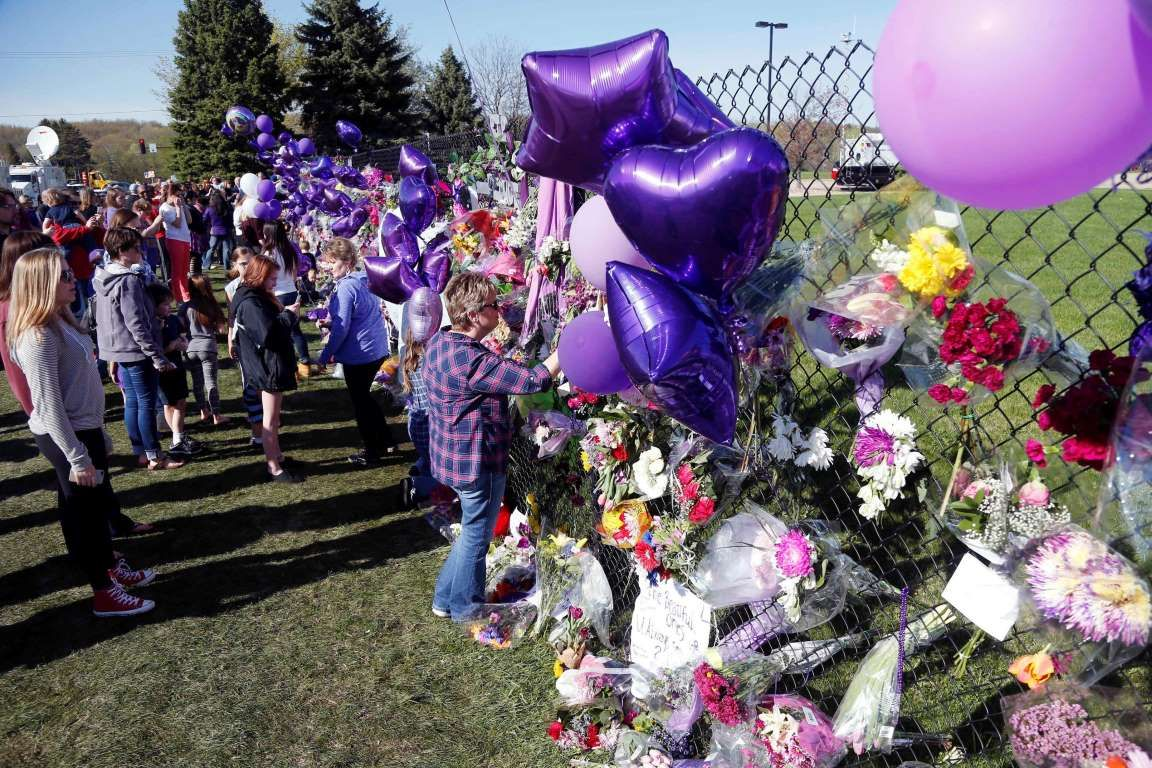 A memorial fence in memory of pop star Prince is lined with flowers and signs at Paisley Park Studios Friday, April 22, 2016 in Chanhassen, Minn. Prince died Thursday at Paisley Park at the age of 57. (AP Photo/Jim Mone)