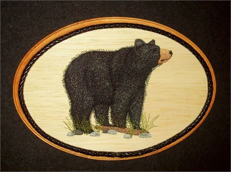 This unique Black BearEmbroidery Wood Art, Wildlife Wall Decor combines the warmth of wood with the raised texture of 11 different thread colors and 23,453 stitches. The design was machine embroidered into a sheet of balsa wood, then cut and mounted on an oak stained 7 x 9 x 1 plaque. The black leather braided trim was added before a clear protective, non-yellowing acrylic matte finish was applied. A brass hanger is attached to the backside making it ready for hanging.    Balsa Wood…