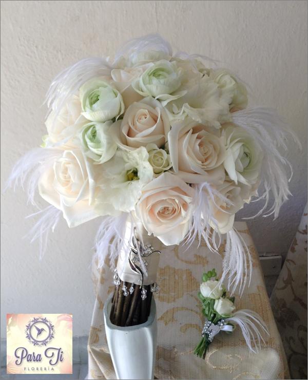 Bouquet de rosas véndela, ranúnculos y lisianthus con detalle de plumas de avestruz y broche plata. A un lado el boutonnier del novio