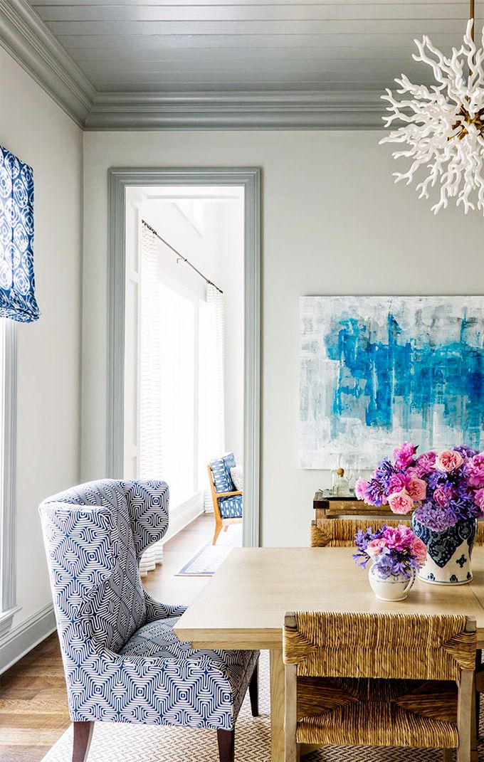 Coral chandelier over dining room with bouquet of colorful flowers, blue artwork, white room and  patterned armchair at the end of the table