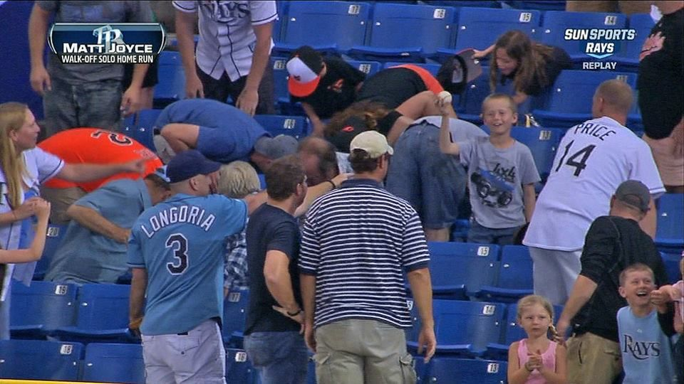 Little boy holds up homerun ball as the section tries to find it.