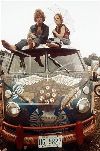 Concert-goers sit on the roof of a Volkswagen bus at the Woodstock Music and…