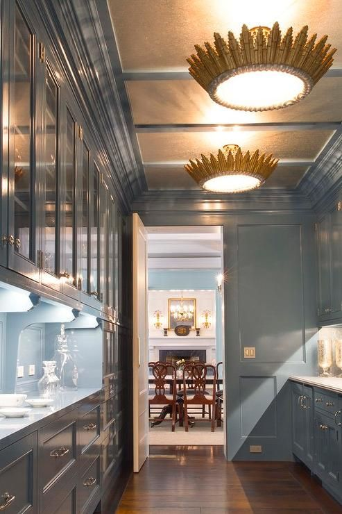 Long, blue butler's pantry features a gold paneled ceiling accented with a  gold semi flush mount lights illuminating blue lacquered cabinets.